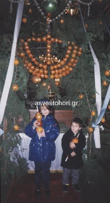 Παιδιά με κεριά στολισμένα με πορτοκάλια και μήλα